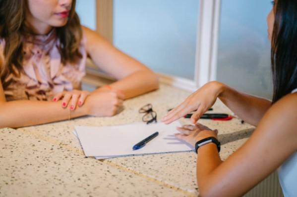 Mujeres hablando con notas