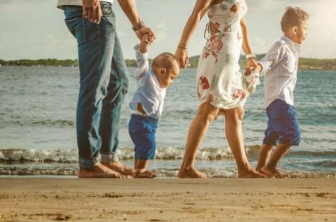 Madre y padre paseando con niños en la playa