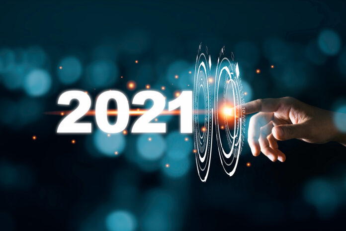 A hand touches a virtual interface rippling forward into 2021.
